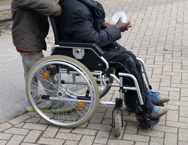 man sitting in a wheelchair being assisted by another person